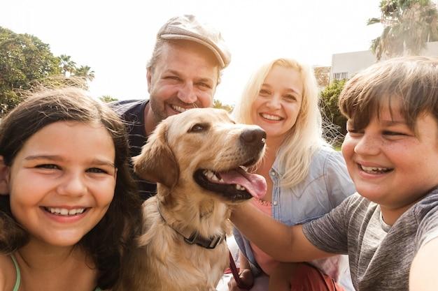夏の時間に公園で子供とペットを楽しむ若い親