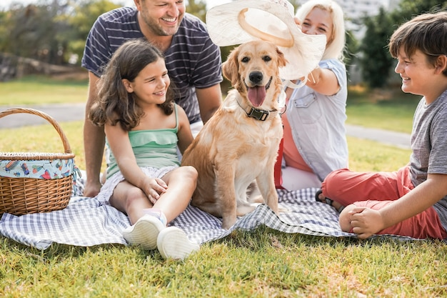 Young parents having fun with children and their pet outdoor at park in summer time