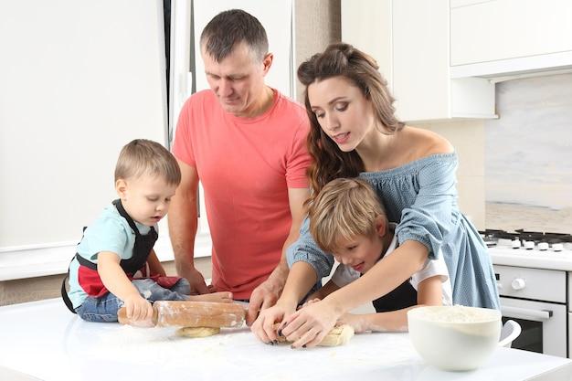 젊은 부모는 어린 아들이 식탁에서 반죽을 반죽하도록 도와줍니다.