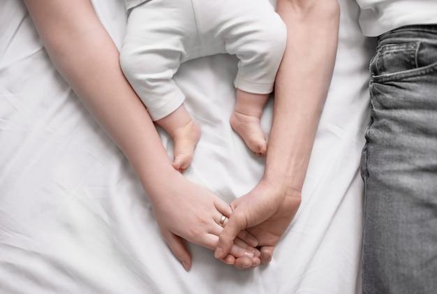 一緒に手をつないでいる若い親と自宅のベッドに横たわっているかわいい赤ちゃん