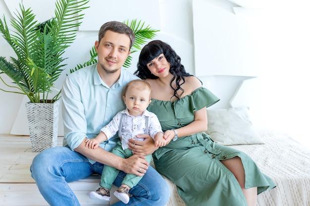 Молодые родители обнимают ребенка в светлой комнате в зеленой одежде, концепция счастливой семьи, день семьи