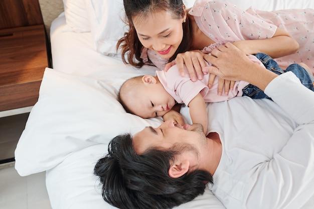 Молодые родители обнимают своего мальчика, почти спящего между ними на удобной мягкой кровати