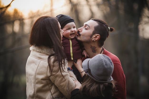포즈를 취하는 동안 아기를 키스하는 젊은 부모