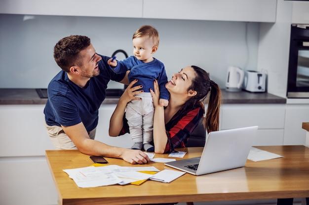 愛する一人息子の助けを借りて、家にオンラインで請求書を支払う若い親。ホームインテリア。