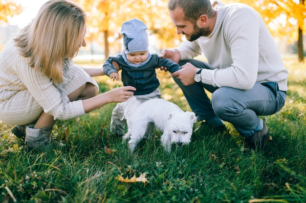 Young  parents playing with their child in autumn park.