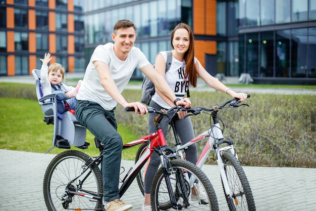Young parents ride a bicycle with a small daughter on city streets