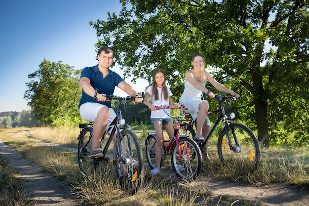 Young parents riding on bicycles with their daughter at meadow