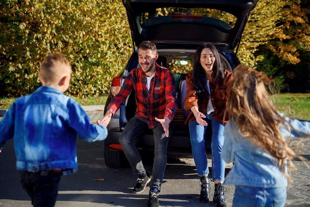 Young parents sitting in the car's trunk and catch to embrace their happy son and daughter
