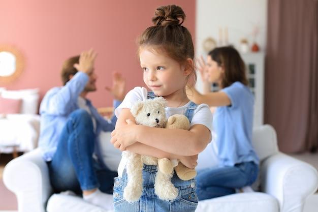 Молодые родители сидят друг напротив друга на диване, громко ругаются и жестикулируют руками, в то время как маленькая беззащитная дочь расстроена, глядя в камеру.