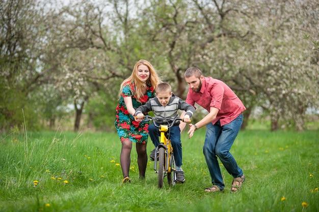 Молодые родители учат сына кататься на велосипеде