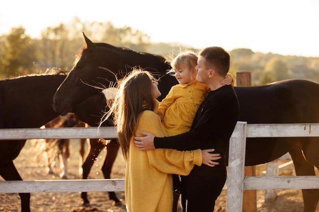 Молодые родители гуляют с маленькой дочкой возле лошадей в осеннем парке.