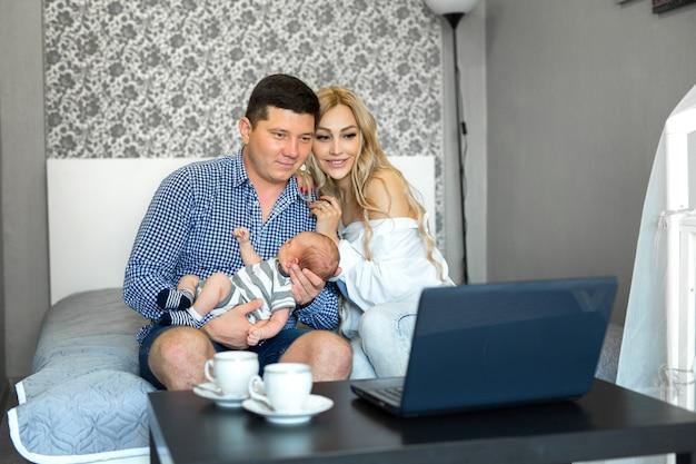 Молодые родители с младенцем дома за ноутбуком