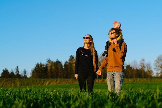 Молодые родители с маленьким сыном гуляют по полю на закате летом. понятие семьи