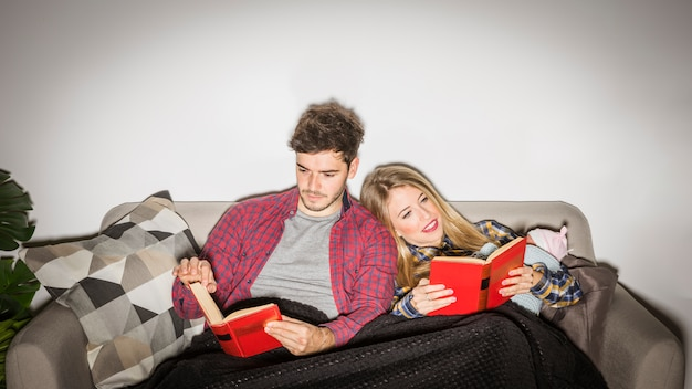 Young parents with baby reading books