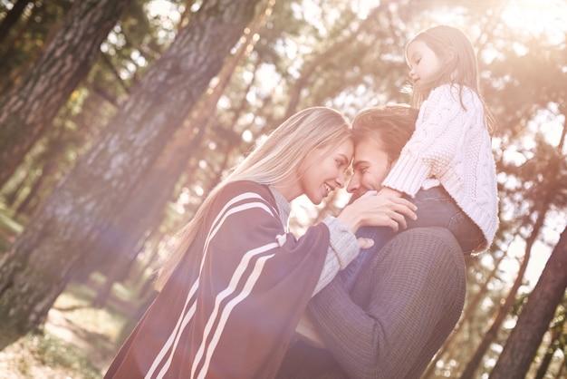Молодые родители с маленькой дочкой в осеннем лесу. отец держит девочку, мама идет рядом и трогает ее за руку