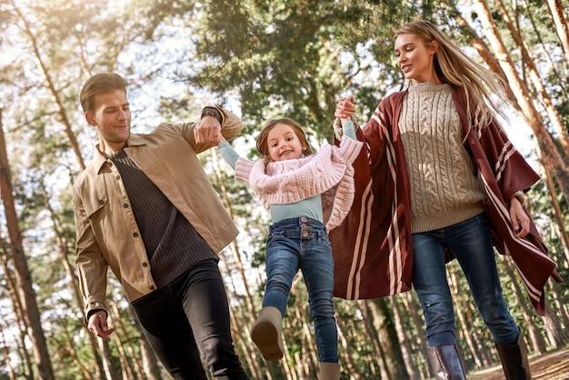 秋の森で幼い娘を持つ若い親。女の赤ちゃんを抱いてママとパパ。底面図