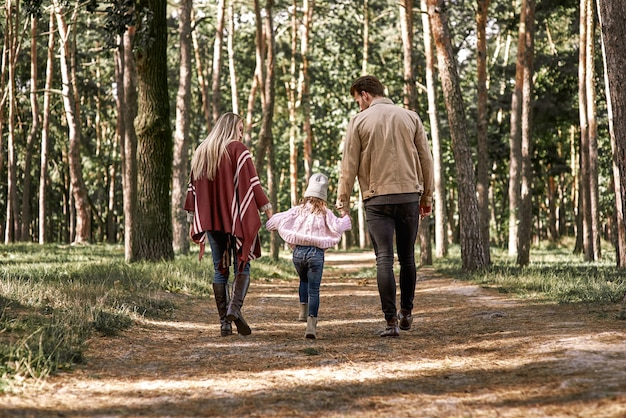 秋の森で幼い娘を持つ若い親。女の赤ちゃんを抱いてママとパパ。背面図