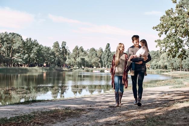 Молодые родители с маленькой дочкой в осеннем лесу у озера. отец держит девочку, мама идет рядом и касается ее руки слева