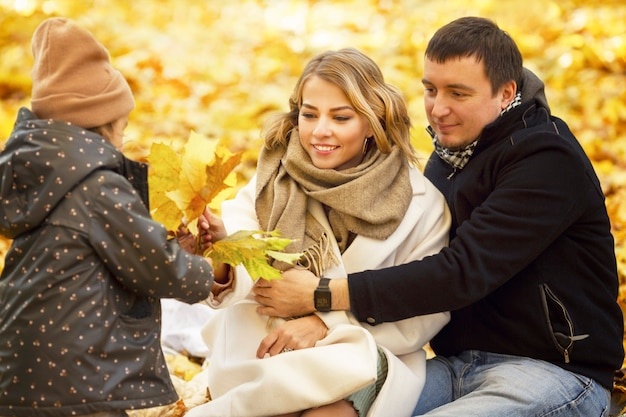 Young parents with their little daughter in the autumn park collect beautiful multi-colored maple leaves. smiling happy family on a walk on a sunny day.