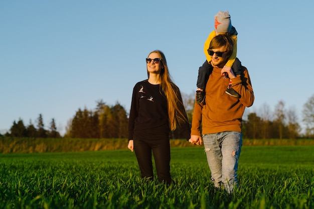 Young parents with a young son walking on a field at sunset in the summer. concept of family