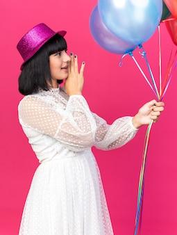 ピンクの壁に隔離された側のささやきを見て風船を保持している口の近くに手を保ち、縦断ビューで立っているパーティーハットを身に着けている若いパーティーの女の子