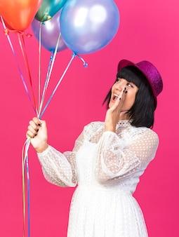 ピンクの壁に隔離された誰かに声をかけて見上げる風船を持って口の近くに手を保ち、縦断ビューで立っているパーティーハットを身に着けている若いパーティーの女の子