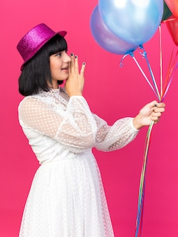 Young party girl wearing party hat standing in profile view keeping hand near mouth holding balloons looking at side whispering isolated on pink wall