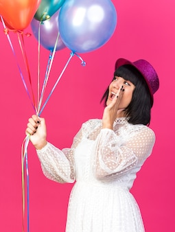 Young party girl wearing party hat standing in profile view keeping hand near mouth holding balloons looking up calling out to someone isolated on pink wall