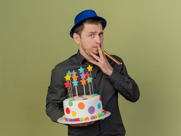 검은 셔츠와 케이크를 들고 파란색 모자를 쓰고 올리브 그린에 고립 된 파티 송풍기를 불고있는 젊은 파티 남자