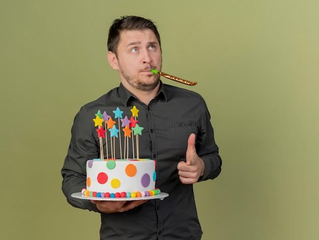 올리브 그린에 고립 된 제스처를 보여주는 휘파람을 불고 케이크를 들고 검은 셔츠와 파란색 모자를 쓰고 젊은 파티 남자