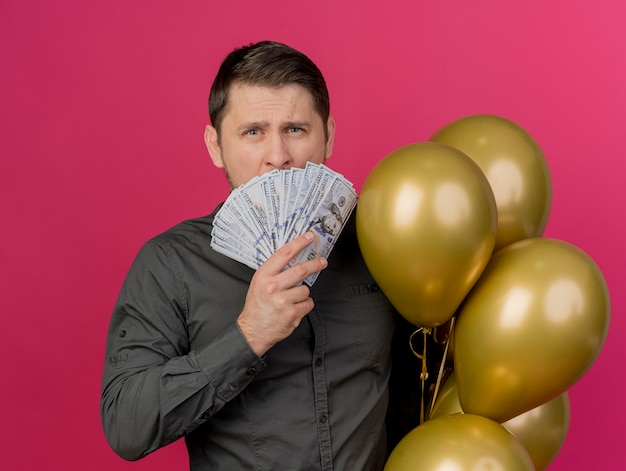 Young party guy wearing black shirt holding balloons covered face with cash isolated on pink