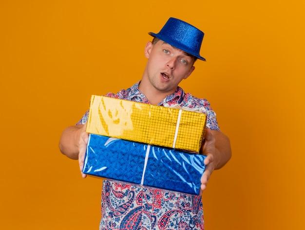 Ragazzo giovane partito che porta il cappello blu che tiene fuori i contenitori di regalo isolati sull'arancio