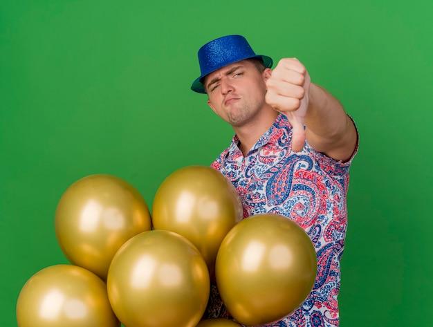 Ragazzo giovane partito che indossa cappello blu isolato sul verde