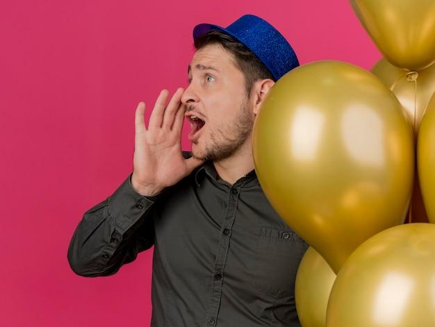 Молодой тусовщик в синей шляпе стоит рядом с воздушными шарами и зовет кого-то изолированным на розовом