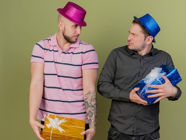I giovani ragazzi del partito che indossano il cappello del partito si guardano l'un l'altro tenendo i contenitori di regalo isolati su fondo verde oliva