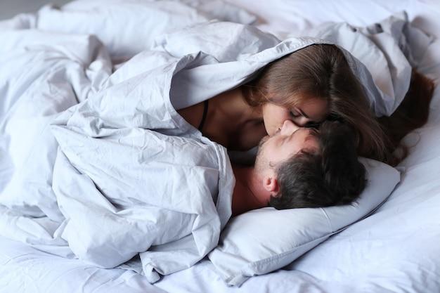 Молодая влюбленная пара целуется в постели