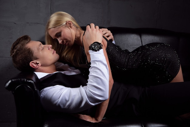 Young passionate lovers gently kiss on a black leather sofa