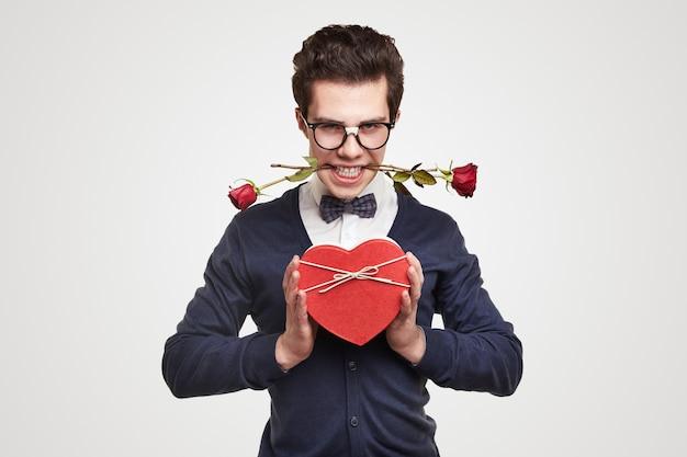 Молодой страстный хорошо одетый мужчина в очках ботаника с красными розами во рту представляет подарочную коробку в форме сердца во время приветствия в день святого валентина.