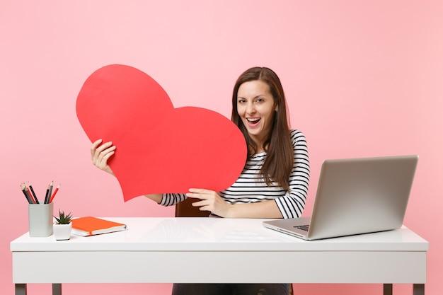 La giovane donna appassionata che tiene il cuore in bianco vuoto rosso si siede e lavora alla scrivania bianca con un computer portatile pc