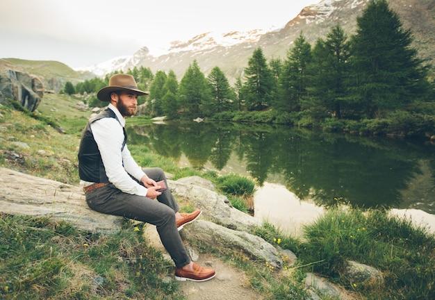 Молодой пастор-проповедник держит библию и смотрит на горы