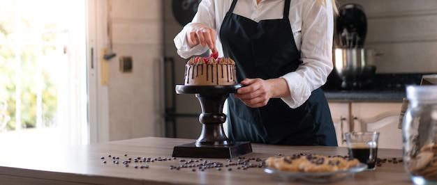 Молодой кондитер готовит вкусный домашний шоколадный торт с фруктами на кухне