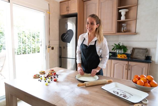 Молодой кондитер готовит сладкий торт на кухне