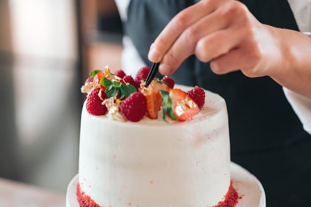 Молодой кондитер готовит традиционный красный бархатный торт на кухне