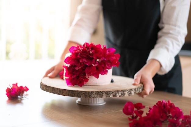 台所で伝統的なレッド ベルベット ケーキを調理する若いパティシエ