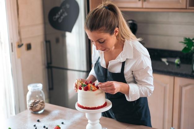 キッチンで伝統的なレッドベルベットケーキを調理する若いパティシエ