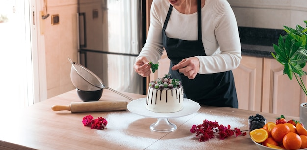 Young pastry chef cooking a delicious homemade white chocolate cake with fruits in the kitchen