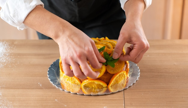 Young pastry chef cooking an orange cake with sliced oranges