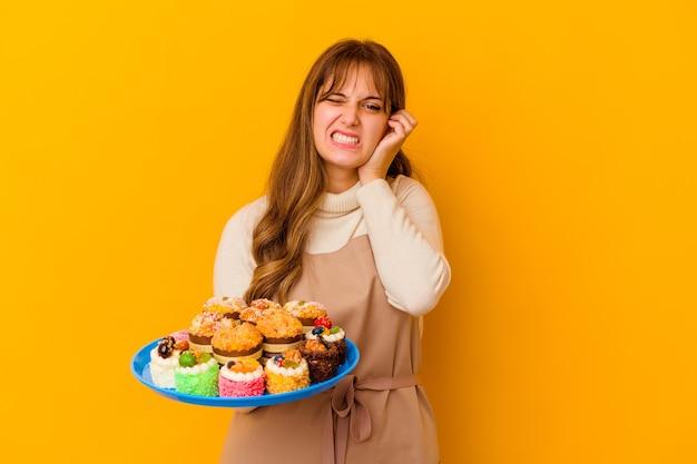 손으로 귀를 덮고 노란색 벽에 고립 된 젊은 생 과자 요리사 여자