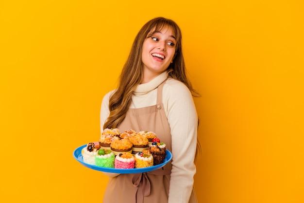 黄色の壁に隔離された若いパティシエの女性は、笑顔、陽気で楽しい脇に見えます。