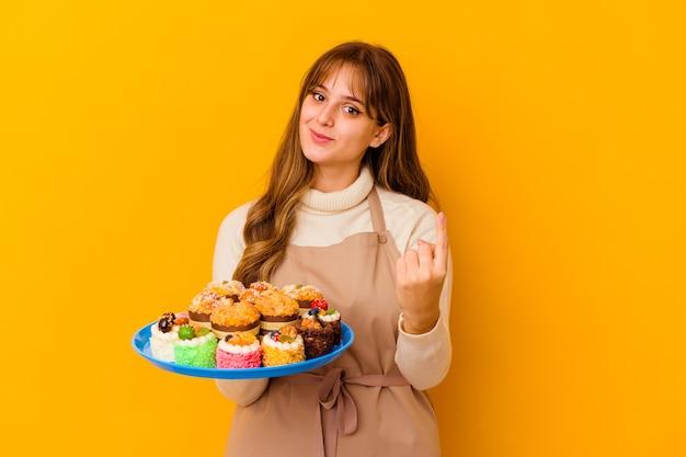 黄色い壁に孤立した若いパティシエの女性が、誘うように指であなたを指さします。